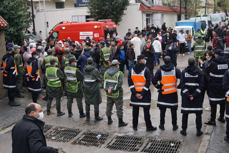 Emergency services gather at the site of illegal underground textile workshop that flooded after heavy rain fall in Morocco's city of Tangiers on February 8, 2021. - At least 24 people died after heavy rain flooded an illegal underground textile workshop in a private house in Morocco's port of Tangiers, the state news agency reported. Rescue workers recovered 24 bodies from the property and rescued 10 survivors who were taken to hospital, the MAP agency said citing local authorities. A search of the premises was continuing. (Photo by - / AFP)