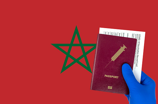 Hand with surgical glove holding a passport with syringe symbol and a vaccination record card or immunization certificate. Morroco flag on background