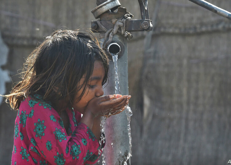 A Pakistani girl drinks water from a hand water pump in Lahore on March 22, 2019, on World Water Day. - Each year on March 22, World Water Day is observed around the world, focusing on the importance of fresh water and advocating for sustainable management of water resources. (Photo by ARIF ALI / AFP)